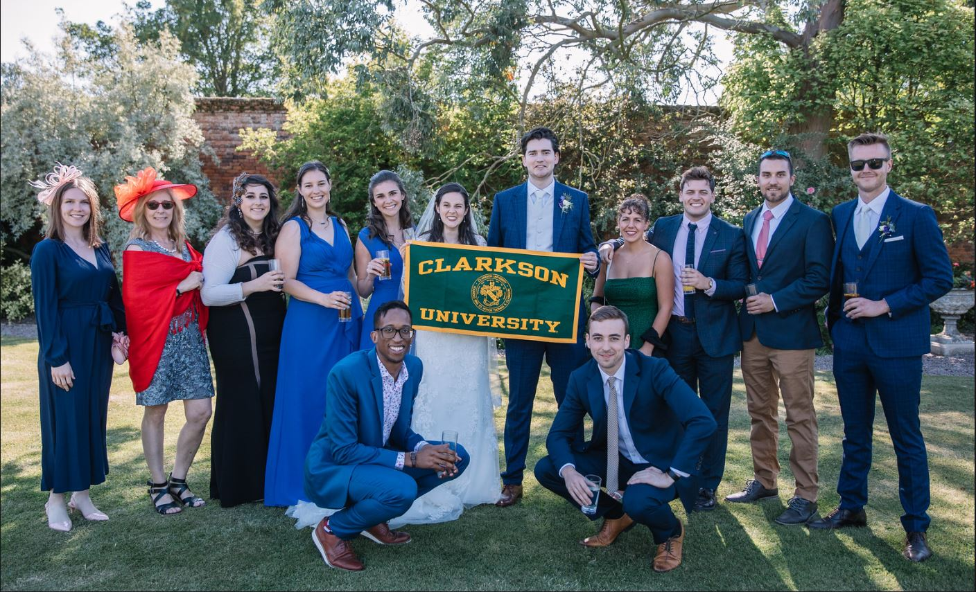 Wedding group photo. Bride and Groom are holding Clarkson University Banner