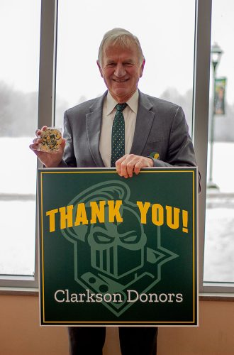 Clarkson University President Tony Collins participating in the first Grateful Golden Knights day by holding a thank you sign and a golden knight cookie.